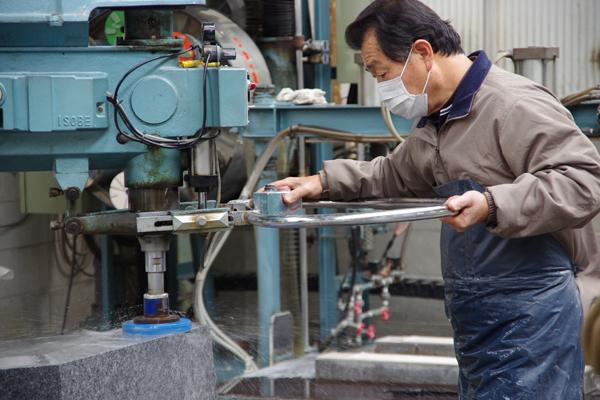 石を磨く機械とその機械を操る職人さん